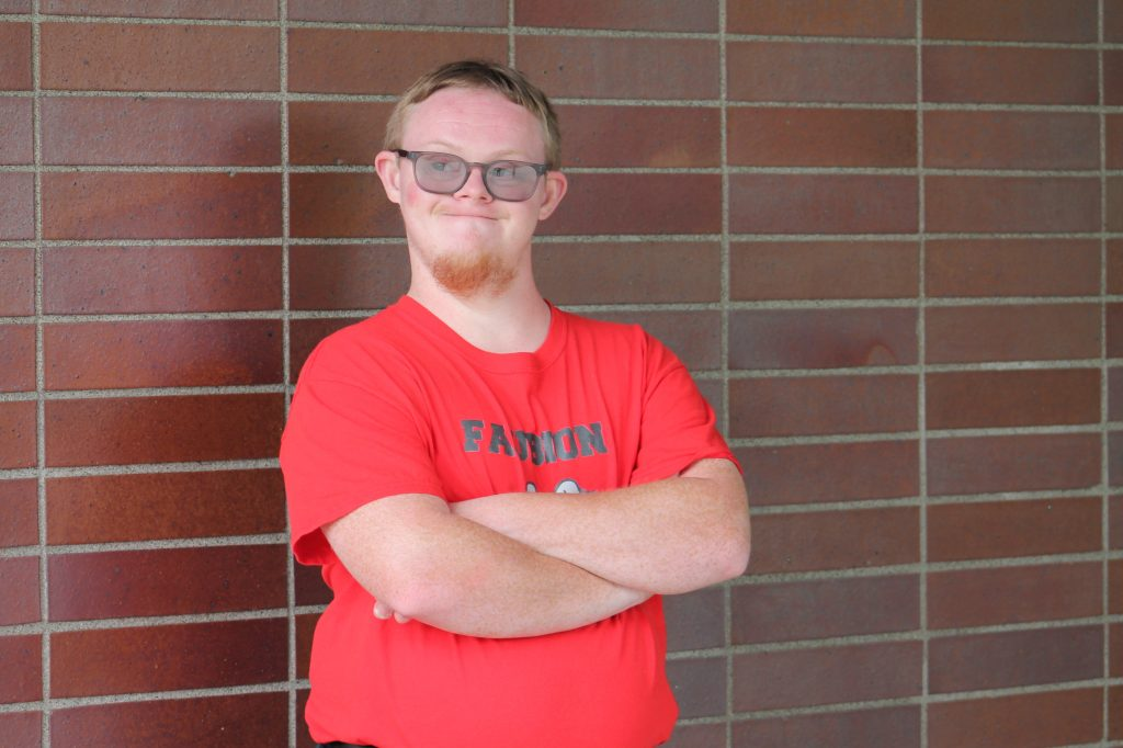 Cody stands with his back to a brick wall, his arms cross over a red T-shirt as he looks off to the left.