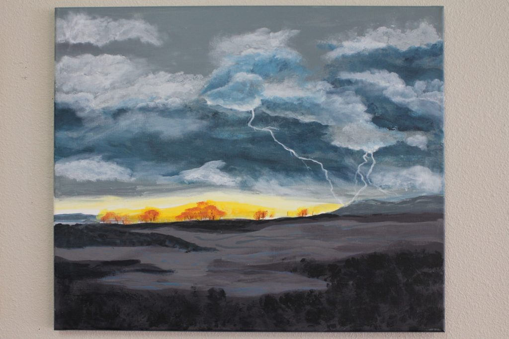 A landscape painting of a storm with a yellow break in the clouds where the sky meets the black ground.