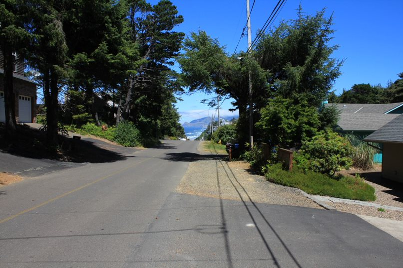 The driveway of the Beach House connects to a road with a view of large hills and Lincoln City in the distance. There are several large trees that hang tall over the road to provide some shade on a sunny day.