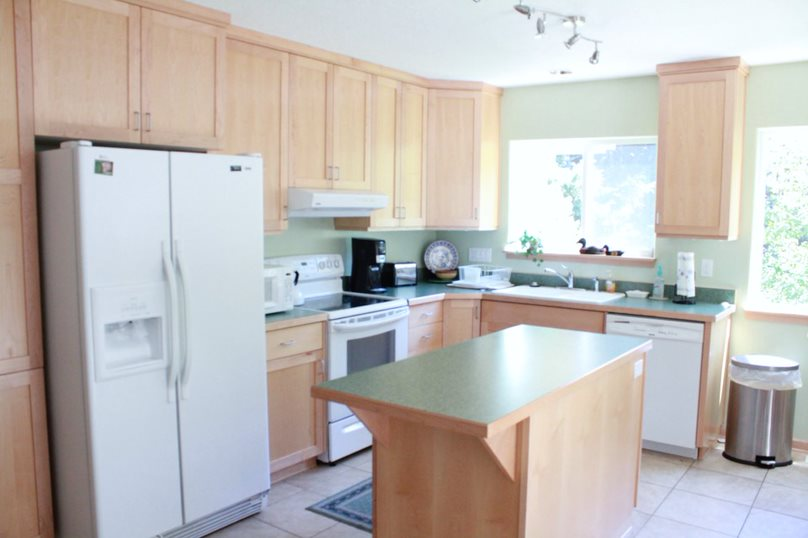 A fully functional kitchen, complete with basic amenities like a stove and oven, dish washer, coffee pot, microwave, refrigerator, trash can and kitchen island. Two large windows let in plenty of natural lighting.